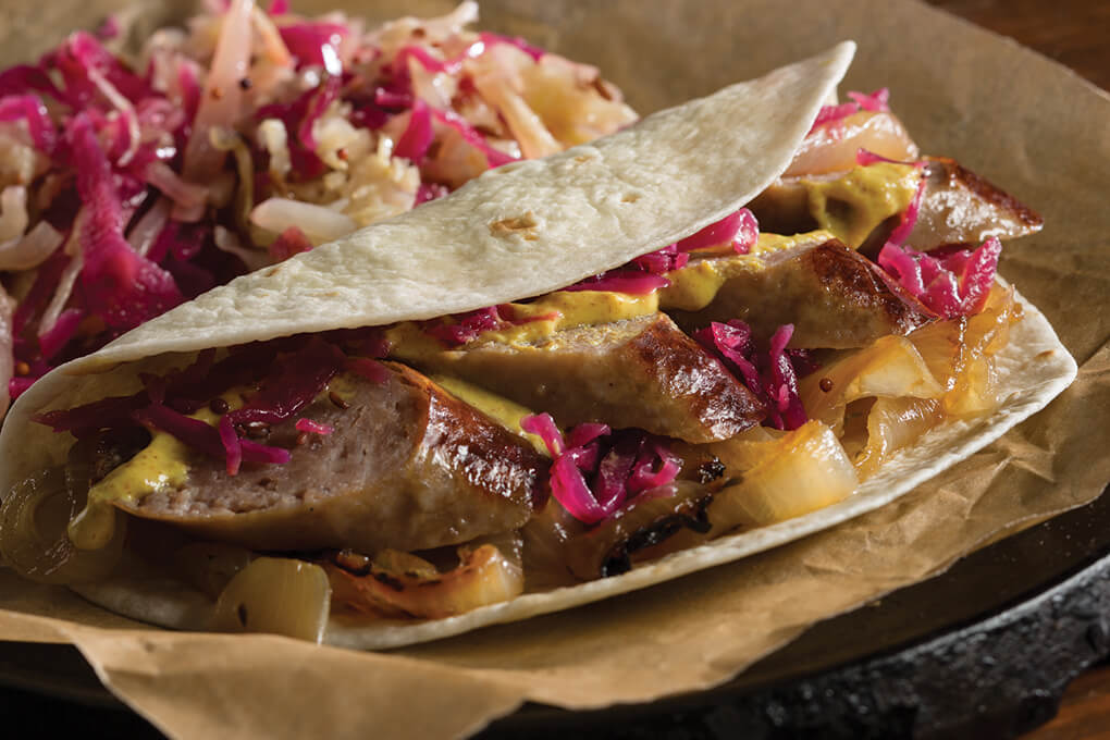A touch of global fusion updates this beer-braised German bratwurst, served handheld-style inside a tortilla.