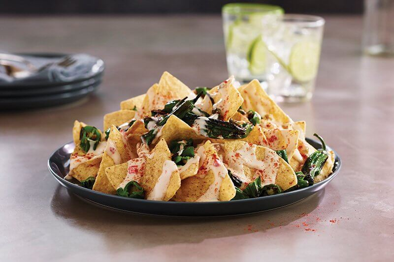 White Cheddar Shishito Nachos showcase how on-trend substitutions can take nachos in a wonderful new direction.