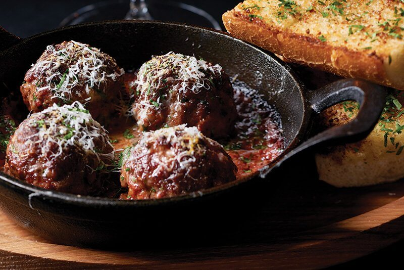 Dry-Aged Prime Beef Meatballs in a cast-iron skillet were inspired by Chef Danny Grant's family recipe, served at Maple & Ash in Chicago.