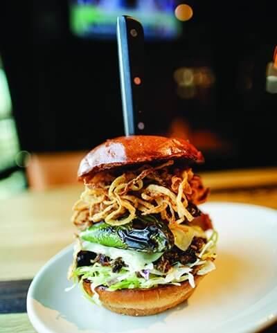 "Dubbed ""The Ultimate,"" Wood Ranch's new sandwich includes Carolina pulled pork, Carolina slaw, brisket, Swiss cheese, kielbasa, charred jalapeño and onion strings."