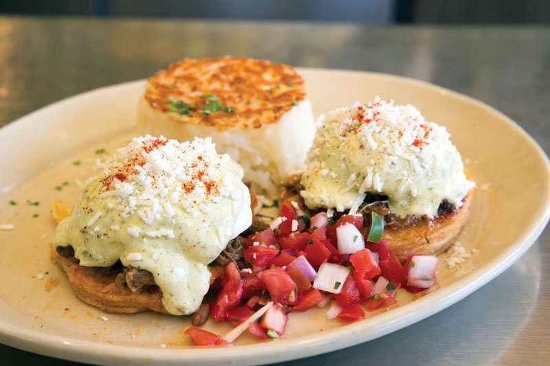 Both bold and comforting, Chilaquiles Benedict at Denver-based Snooze incorporates barbacoa, tortillas draped in ranchero sauce, poached eggs, poblano hollandaise and pico de gallo.