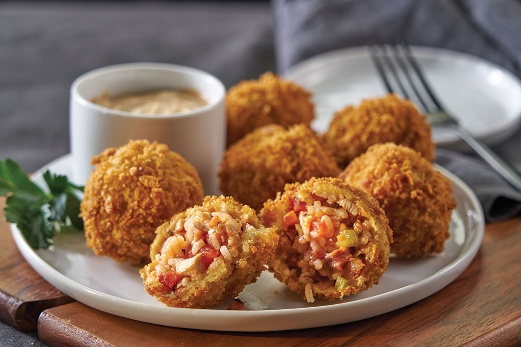 Jambalaya Arancini captures Cajun flavors in a craveable Italian-style bite, featuring U.S.-grown long-grain white rice, chicken and andouille, served with rémoulade. The rice holds the heat well for takeout and carries bold flavors beautifully.