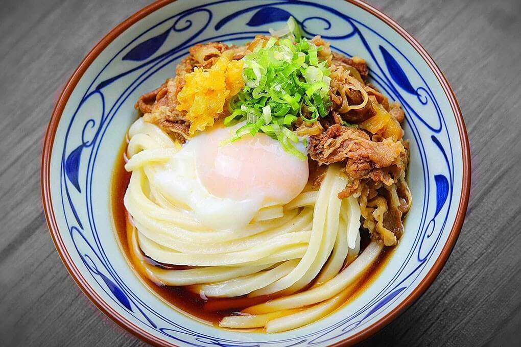 Curry Nikutama Udon with Japanese curries, beef, caramelized onions, a soft- poached egg, tempura flakes and green onions